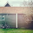 Old bicycle leaning against wooden barn — Stock Photo #63549335