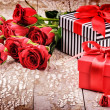 Bouquet of red roses and presents — Stock Photo #63549353