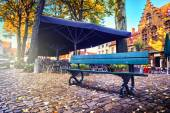 Lonely bench and outdoor cafe — Stock Photo