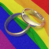 Wedding rings on rainbow banner — Stock Photo
