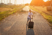 The  happy boy run with a suitcase in a summer sunny day — Stock Photo