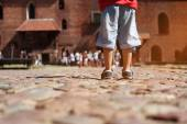 Legs of little kid boy  on the  stone road on the excursion — Stock Photo