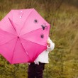 The little girl I hid under a pink umbrella in autumn park — Stock Photo #53873119