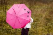 The little girl I hid under a pink umbrella in autumn park — Stock Photo