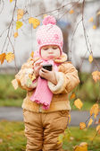 Beautiful little girl holding a phone on autumn park — ストック写真