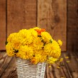 Beautiful bouquet of yellow chrysanthemums flowers in wicker ba — Stock Photo #55152131