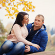 Young loving couple look at each other in warm autumn day — Foto Stock #56907881