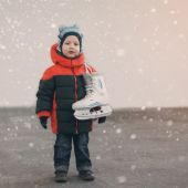 Cute little boy  holds the skates wearing warm winter clothes  g — Stock Photo