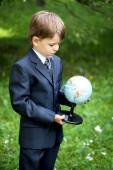 Little boy looking and exploring the globe in nature — Stock fotografie