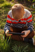 Little kid absorbed into his tablet, outdoor — Photo
