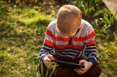 Little kid absorbed into his tablet — Stockfoto