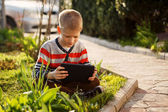Cute boy sitting on grass in park and playing with tablet in ear — Stock Photo