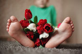 Close up of nurseries a foot with a bouquet of flowers — Stock Photo