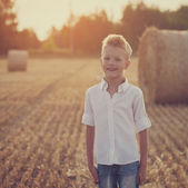 Happy cute boy playing in the wheat field on a warm summer day — Stock Photo