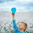 Young boy with paper airplane against blue sky — Stock Photo #73305723
