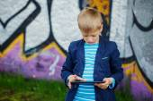 Little boy absorbed into his tablet for educating and playing. — Stock Photo