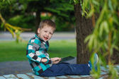 Little smile  boy outdoors  using his tablet computer — Stock Photo