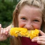 Young Girl Eating Corn — Stock Photo #59974353