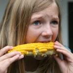Young Girl Eating Corn — Stock Photo #59974355