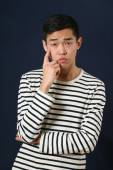 Pensive young Asian man — Stock Photo