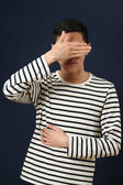 Asian man covering his face — Stock Photo