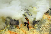 Miner collects sulphur in the fumes — Stock Photo