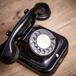 Old black phone with dust and scratches on wooden floor — Stock Photo #51856461