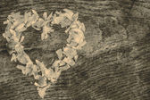 A heart from petals lying on a wooden table — Foto de Stock