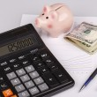 Business Charts with calculator, money, piggy box and pen — Stock Photo #56083361