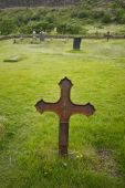 Old rusty cross on graveyard - in the grass — Stock Photo