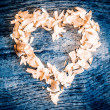 A heart from petals lying on a wooden table — Stock Photo #64540453