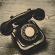 Old black phone with dust and scratches on wooden floor — Stock Photo #65764765