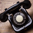 Old black phone with dust and scratches on wooden floor — Stock Photo #66900185