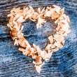 A heart from petals lying on a wooden table — Stock Photo #70195675