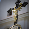 Black cross with gold jesus and chapel as background — Stock Photo #71382991