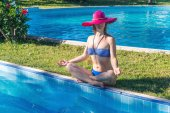 Woman meditating at the pool — Stock Photo