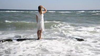 Niña de pie en la playa durante el atardecer hermoso. — Vídeo de Stock