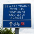 Railway crossing warning sign beware trains cyclists dismount and walk across — Stock Photo #67335147