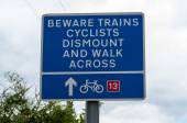 Railway crossing warning sign beware trains cyclists dismount and walk across — Stock Photo