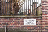 Ivy Road Leading to Laurel Close Street Sign against Brick Wall — Stock Photo