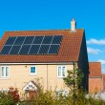 Solar photovoltaic panel array on house roof against a blue sky — Stock Photo #70753571