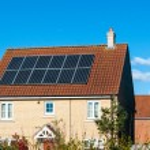 Solar photovoltaic panel array on house roof against a blue sky — Stock Photo #70753731
