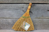 Concept of mismanagement. Broom stuck with dollars — Stock Photo