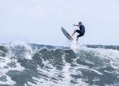 Athlete surfing on a beach — Stock Photo