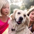 Two little girls with golden retriever dog — Stock Photo #55690379