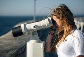 Teenage girl using a tourist telescope — Stok fotoğraf