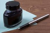 Inkwell and fountain pen on wooden texture. — Stock Photo