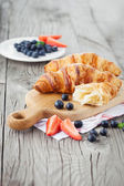Fresh croissants and ripe berries — Stock Photo