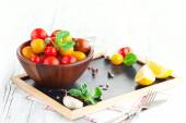 Cherry tomatoes with basil leaves — Stock Photo