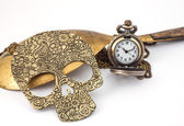 Small watch with chain ,brass ladle,skull necklace on white — Stock Photo